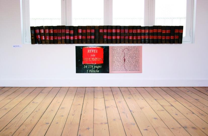 La revue des 2 mondes, 34 576 pages et 1 fétiche, Installation, 36 volumes anciens et deux panneaux imprimés, collés sur toile, 2008